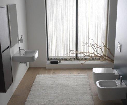un bagno con un bidet e un Wc sulla destra e sulla sinistra un lavandino e uno specchio al muro