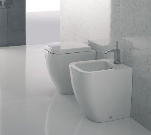 un Wc,un bidet e un pavimento in piastrelle di color bianco