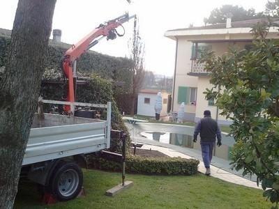 giardino con trattore, gru e un uomo che cammina