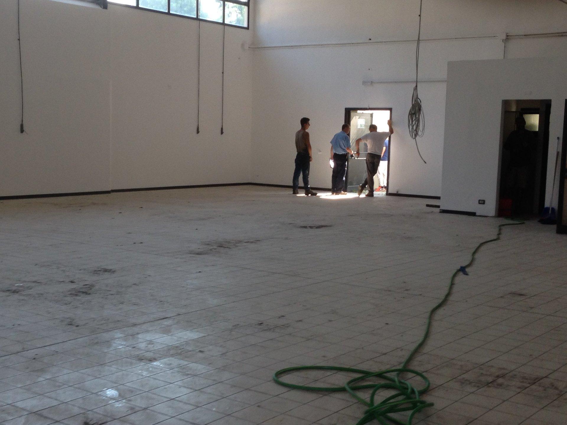 Un uomo mentre utilizza una monospazzola per i pavimenti