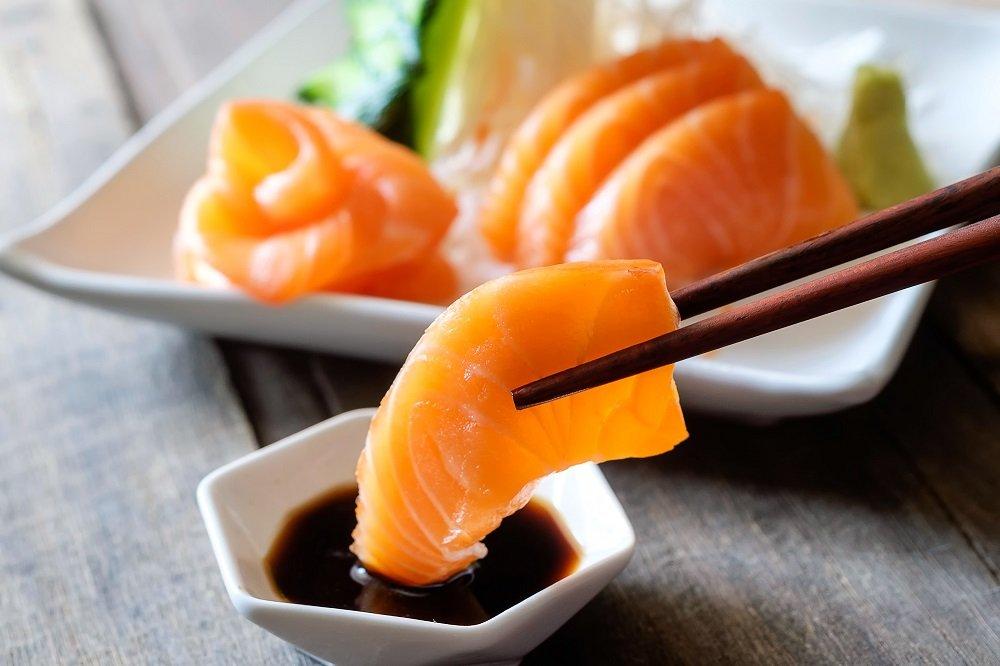 Sashimi, salmone, bacchette e wasabi sul tavolo di legno