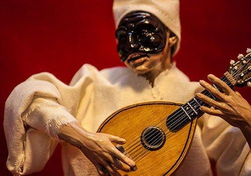 pupazzo pulcinella con chitarra mentre suona