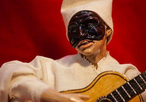dettaglio di pupazzo pulcinella con chitarra