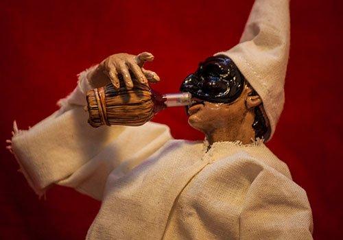 pupazzo pulcinella mentre beve vino da una fiasca