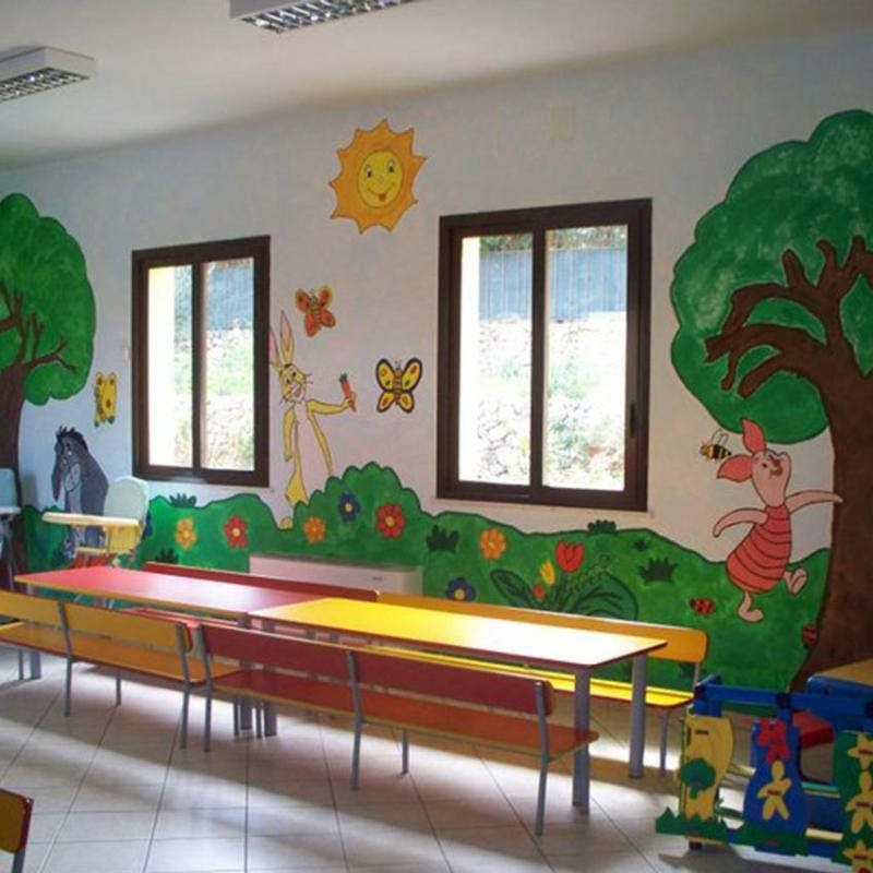 stanza con banchi di scuola e muro colorato a cartone