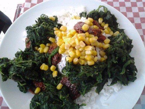 un piatto di riso con spinaci e mais