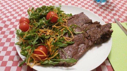 un piatto di bistecca , insalata e pomodorini