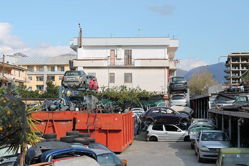 delle macchine incidentate e dei container con degli ammassi di ferraglia