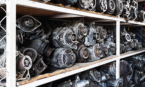 dei motori recuperati dalle auto incidentate dentro a degli scaffali in ferro