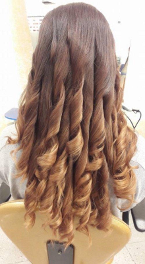 capelli di una donna di color biondo raccolti in su e legati con un fiocco dorato