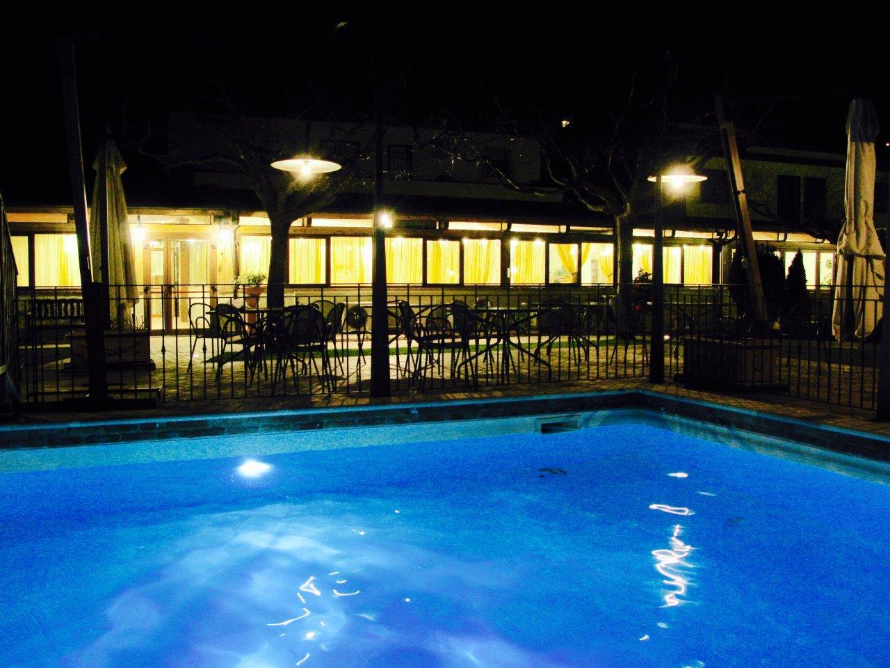 Una piscina con alle spalle un ristorante