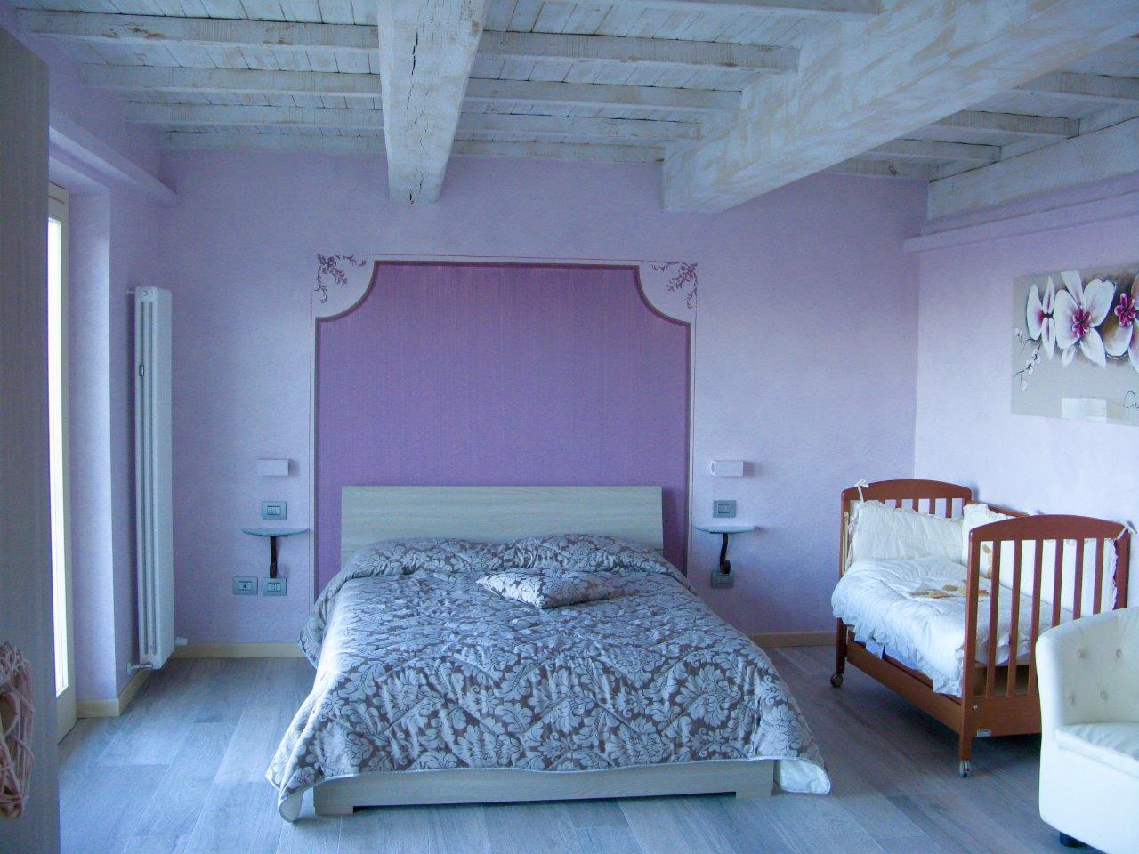 Una camera con un letto matrimoniale ed una culla in legno