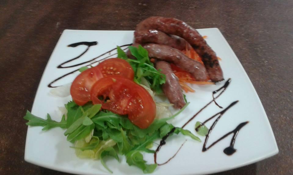 piatto di salsiccie con rucola e pomodori