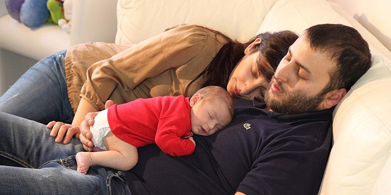 una coppia e un neonato che dormono sul divano