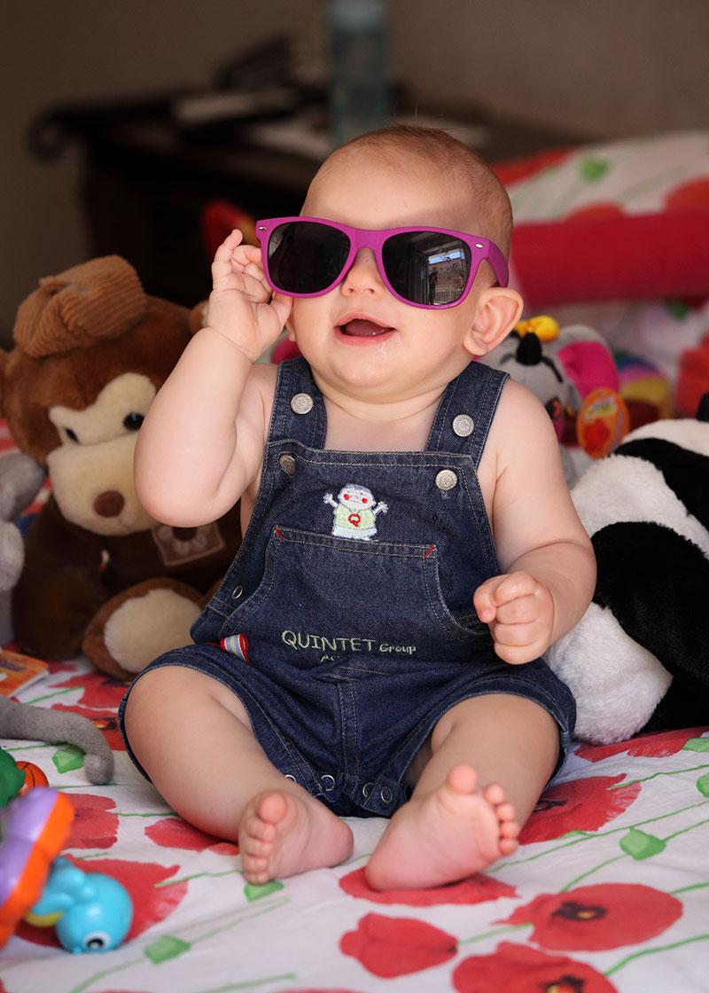 un bambino piccolo con degli occhiali da sole viola