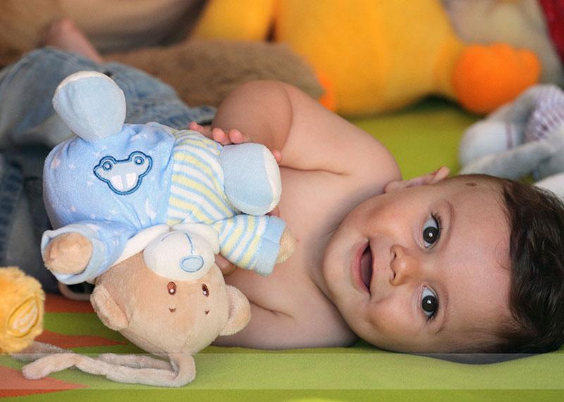 un bambino piccolo sdraiato con un orsetto di peluche