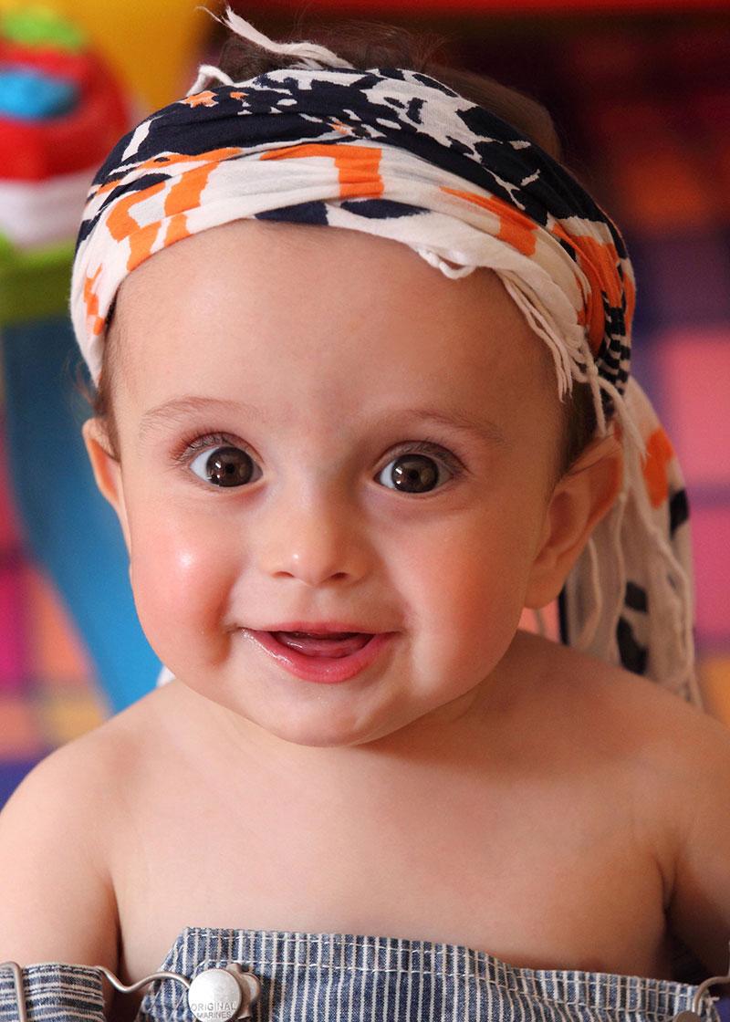 una bambina con un foulard in testa di color nero bianco e arancione