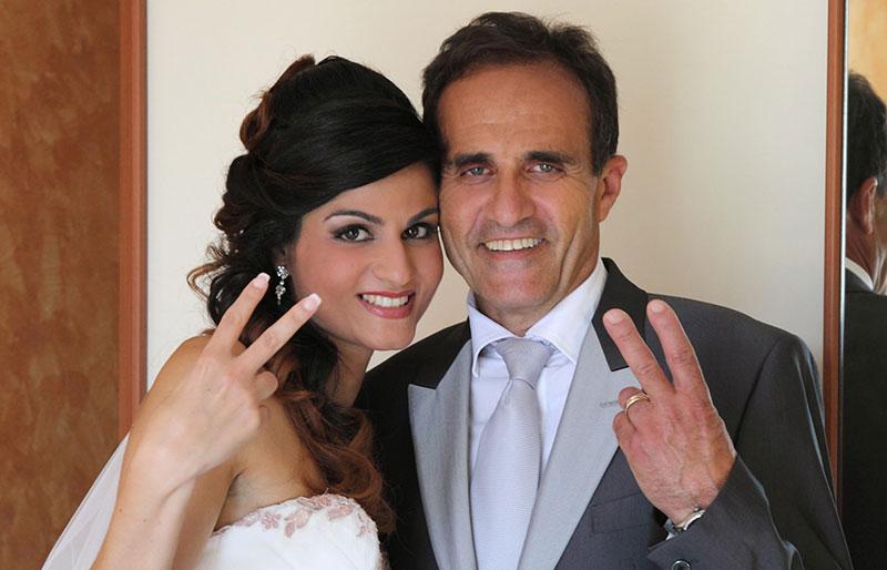 una sposa e accanto un signore in posa per una foto