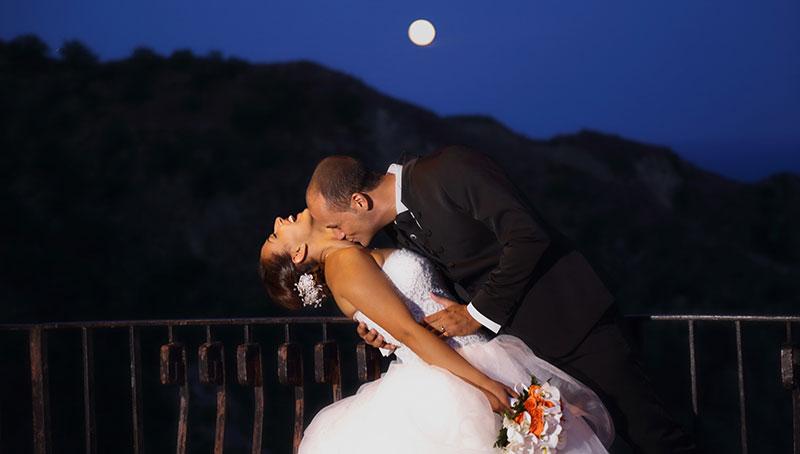 due sposi che si abbracciano e vista della luna