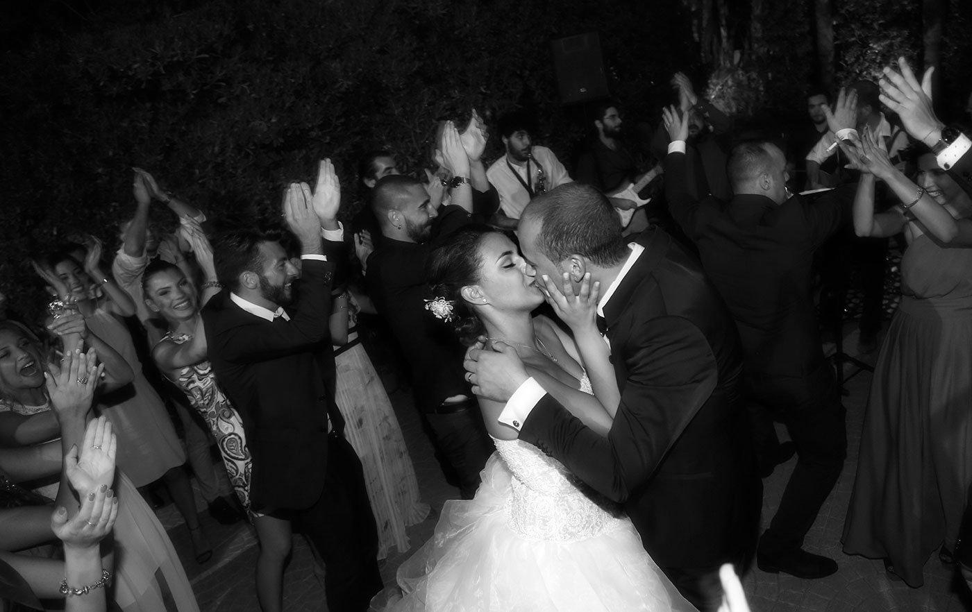 foto in bianco e nero di due sposi che si baciano e gli invitati che ballano