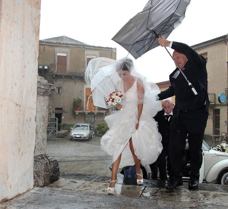 uno sposo con in mano un ombrello e la sposa che cammina