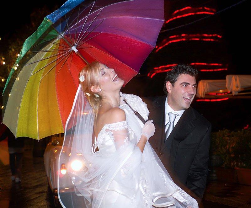 una sposa con un ombrello multicolore mentre ride e accanto lo sposo