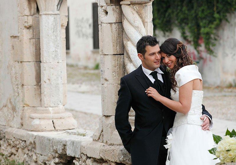 uno sposo e una sposa abbracciati vicino a delle colonne
