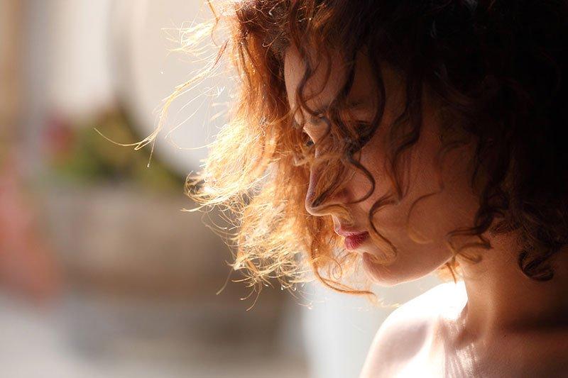 una ragazza con capelli castani mossi vista di profilo