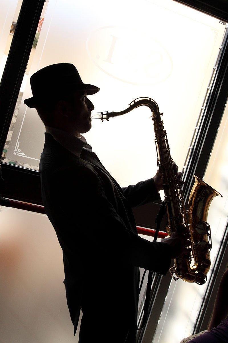un uomo con una bombetta pentre suona un sassofono