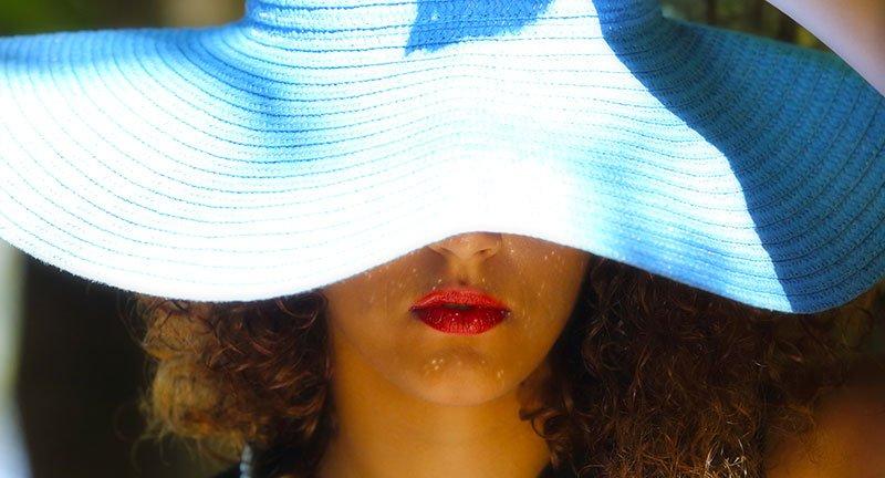 una donna con un cappello di paglia azzurro che le copre il volto