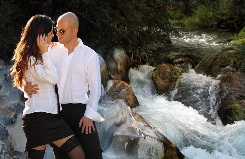 una coppia che si guarda e dietro un ruscello