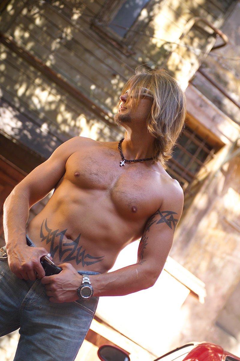 un uomo con capelli biondi lunghi a petto nudo e dei jeans