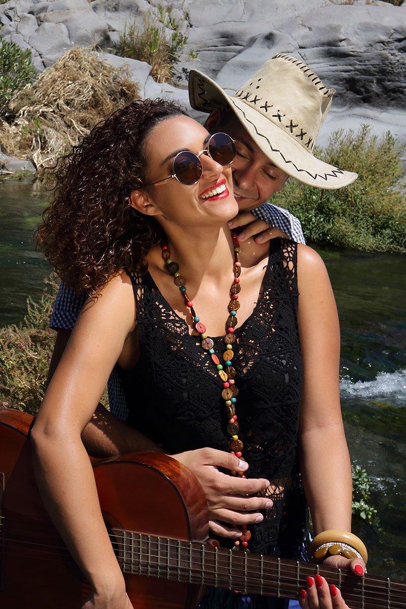 una ragazza con una chitarra in mano e un uomo con un cappello dietro di lei che sta per baciarla sul collo