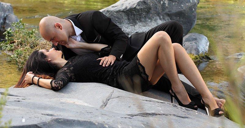 una ragazza sdraiata su una roccia e un uomo che sta per baciarla