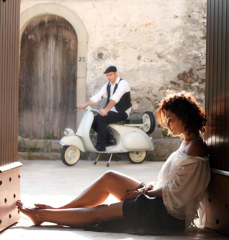 una donna seduta per terra vicino a un portone e un uomo  su uno scooter Vespa fermo