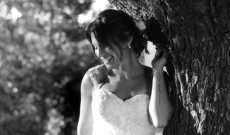 una foto in bianco e nero di una sposa appoggiata su un tronco di un albero