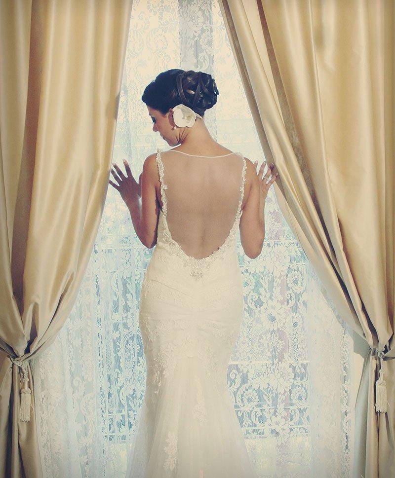 una sposa vista da dietro vicino a una finestra con vista delle tende