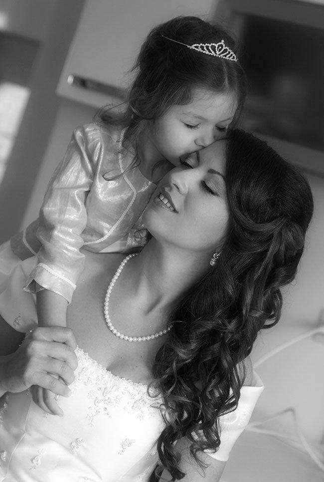 una bambina sulle spalle della mamma mentre le bacia la testa