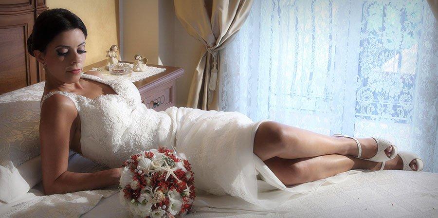 una sposa sdraiata su un letto con un bouquet di fiori