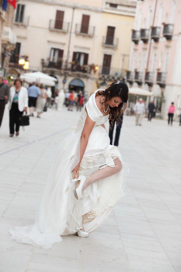 una sposa che si tocca una scarpa in una piazza