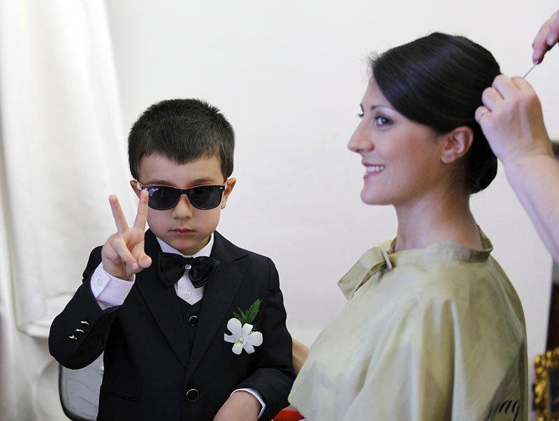 un bambino con un completo,degli occhiali da sole in posa per una foto e accanto una donna seduta