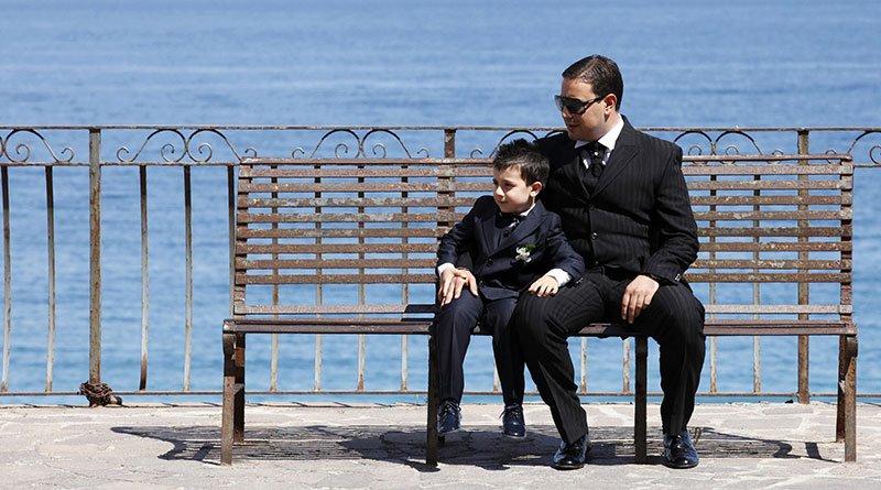 un uomo e un bambino vestiti eleganti seduti su una panchina