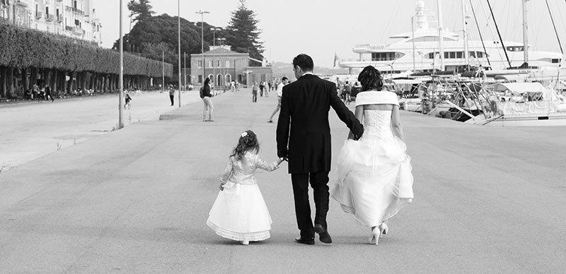 due sposi e una bambina tutti e tre per mano che camminano