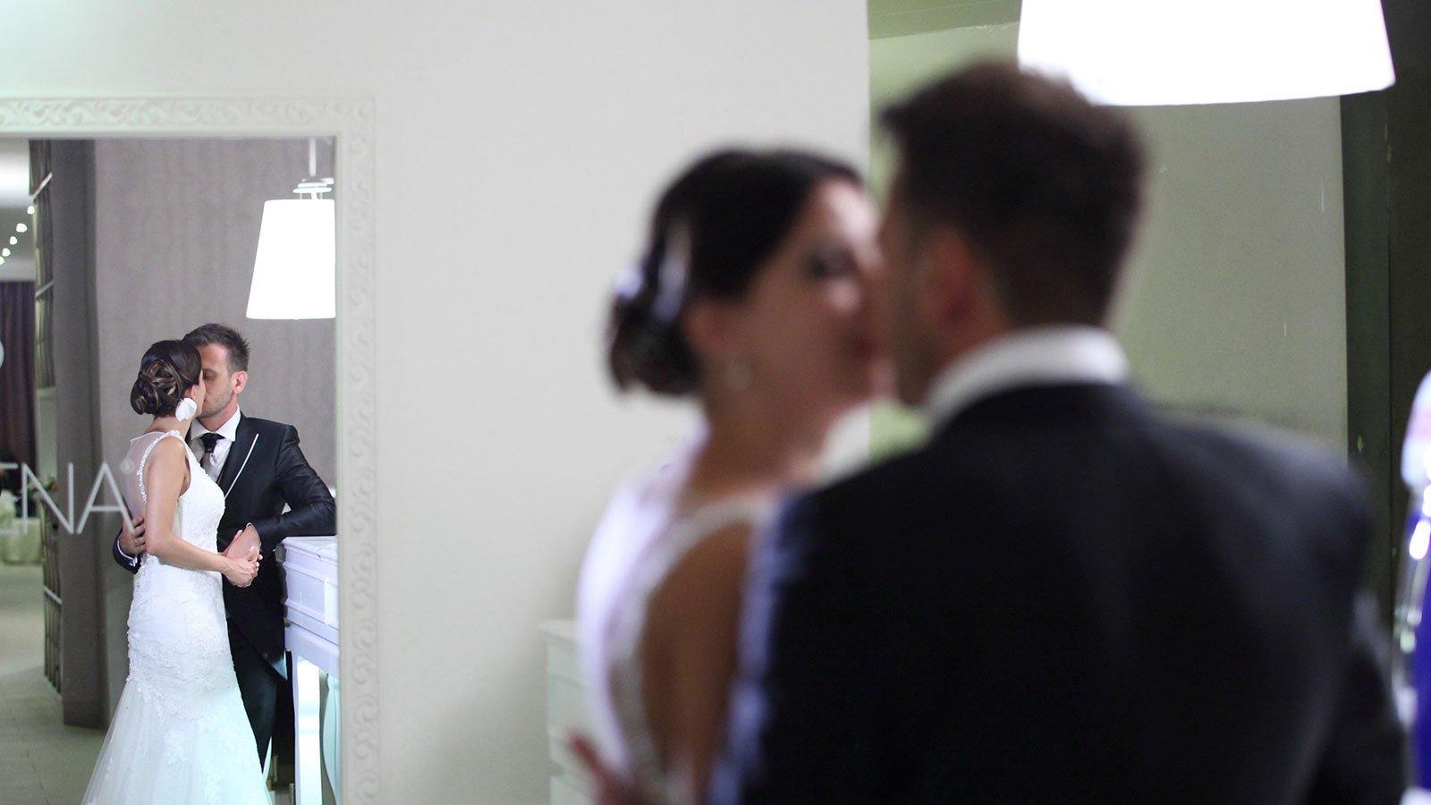 due sposi che si baciano e sulla sinistra uno specchio