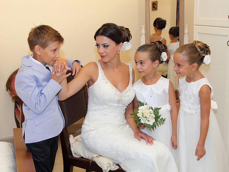 un bambino che bacia la mano di una sposa e accanto delle bambine vestite da damigelle