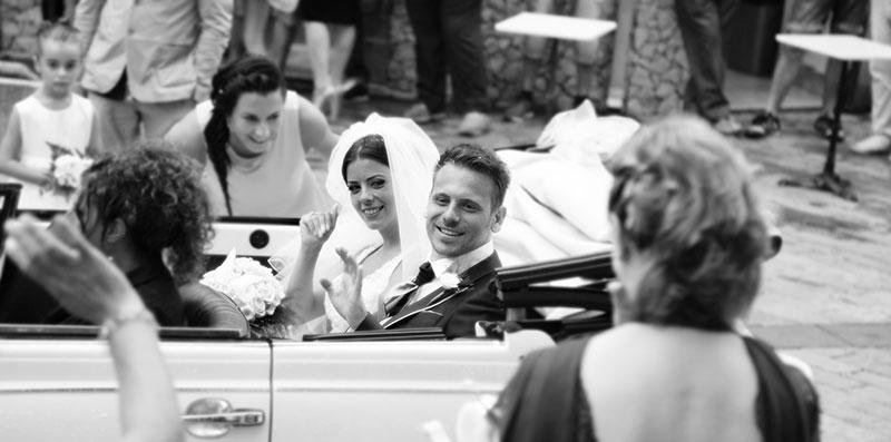 una foto in bianco e nero di due sposi in una macchina