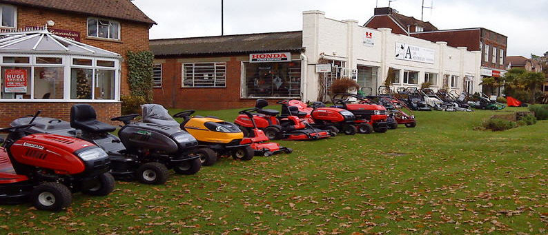 A row of ride-on mowers on leaf-strewn grass outside our premises