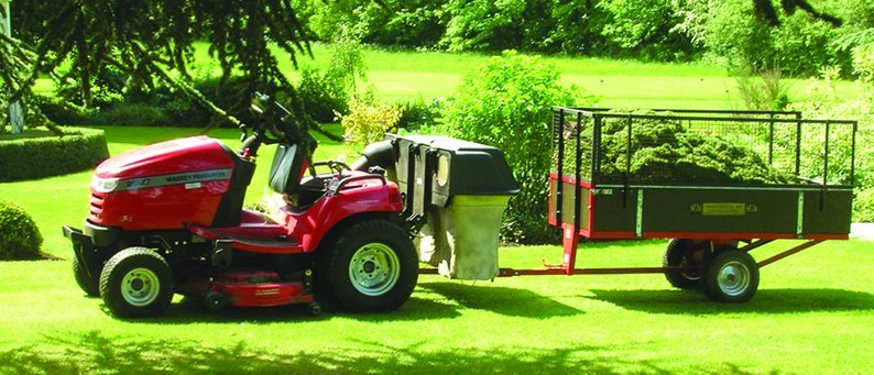 A red ride-on mower with a trailer full of grass, in the middle of a large green lawn surrounded by trees and bushes
