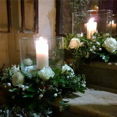 due candele accese con delle ghirlande di fiori intorno