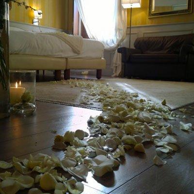 una camera con dei petali di rose bianche sul pavimento e delle candele accese